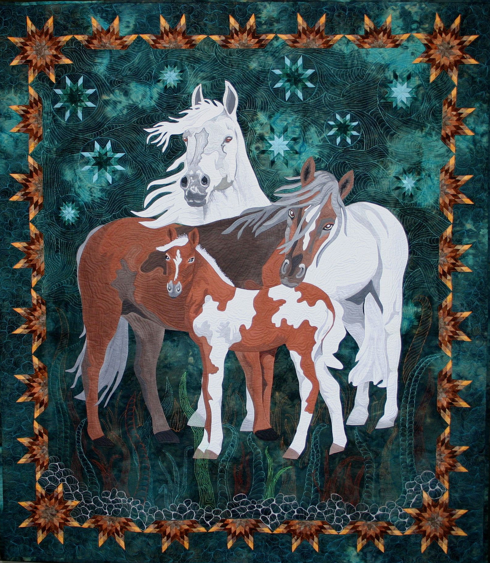 Beauty of the Beast is a fiber art work showing a family of horses the father standing strong the mother leaning to protect her baby and a colt as cute as can be beside them. this was a juried finalist in the Houston International Quilt Show in 2013