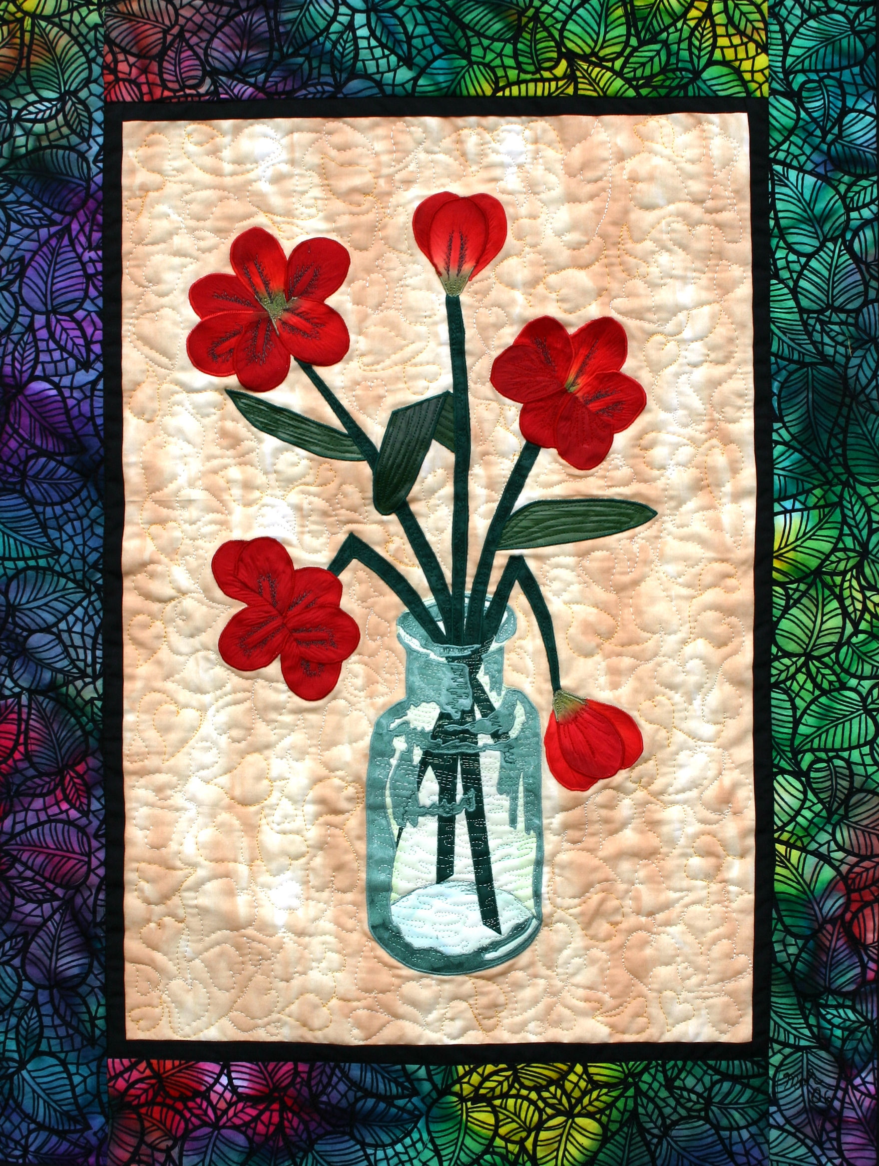 glass vase with flowers is a fiber art work showing some red flowers in a vase with a threadpainted image of glass showing shading and shape with the use of creative stitching
