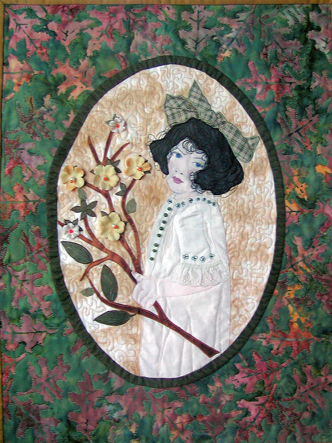 fiber art image of young Victorian Girl holding a branch embellished with three dimensional flowers, with a dress decorated with beads and antique lace