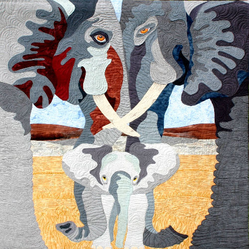Wrapped in Love is a fiber art work showing a mother and father elephant standing head to head with their trunks hanging down and wrapped around their baby elephant. This was a juried finalist in the Houston International Quilt Festival in 2014